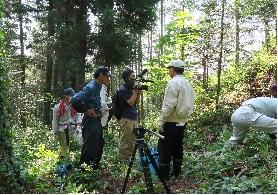 重い機材を抱えて急斜面を上り取材する飯田ケーブルテレビのスタッフ